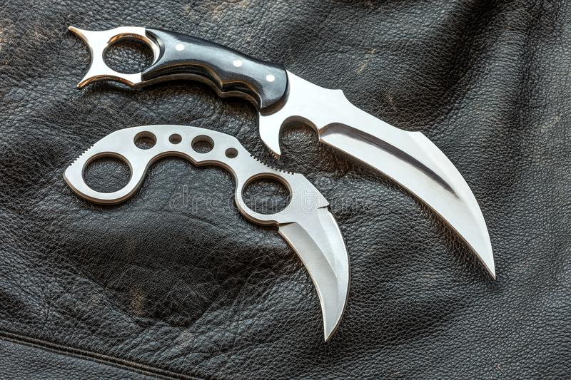 Karambit knives designer made, on a worn leather black jacket stock photo
