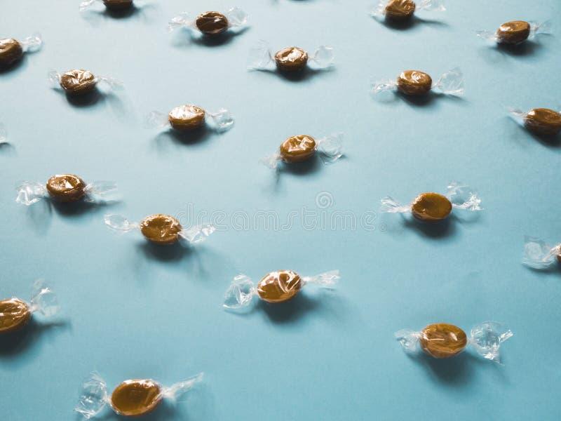 Karamellgodisar på en blå bakgrund royaltyfri foto
