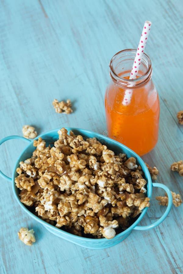 Karamelpopcorn in Blauw Pop Tin Bucket With Orange Soda royalty-vrije stock foto