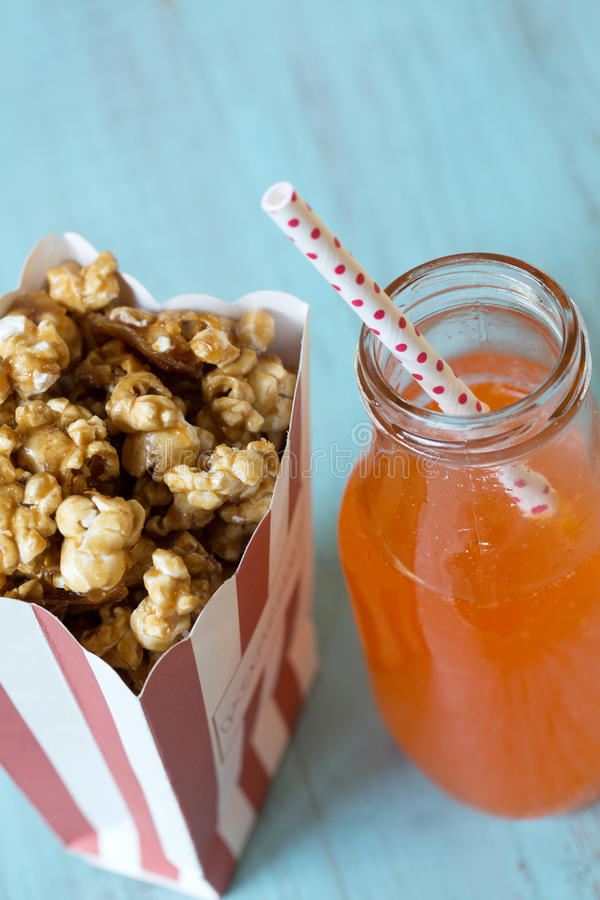 Karamelpopcorn en Oranje Frisdrank met Stro stock fotografie