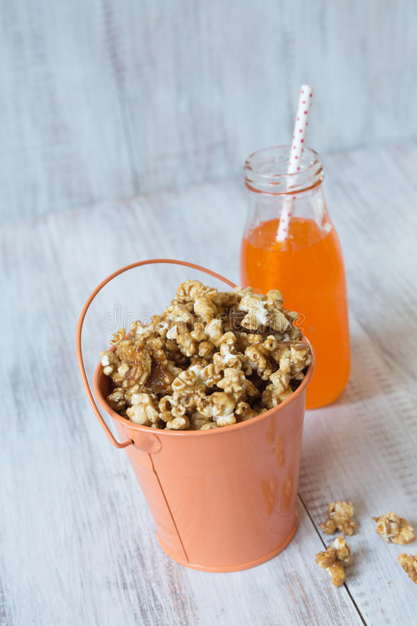 Karamelpopcorn in Pop Snack van Tin Bucket With Orange Soda royalty-vrije stock afbeeldingen