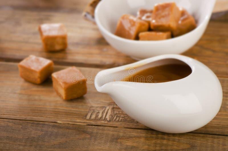 Karamelsuikergoed en saus op rustieke houten lijst royalty-vrije stock afbeelding