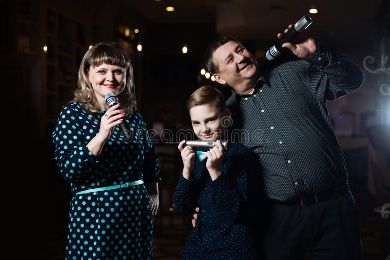 Karaoke da família Retrato de uma família feliz, cantando nos microfones imagens de stock royalty free