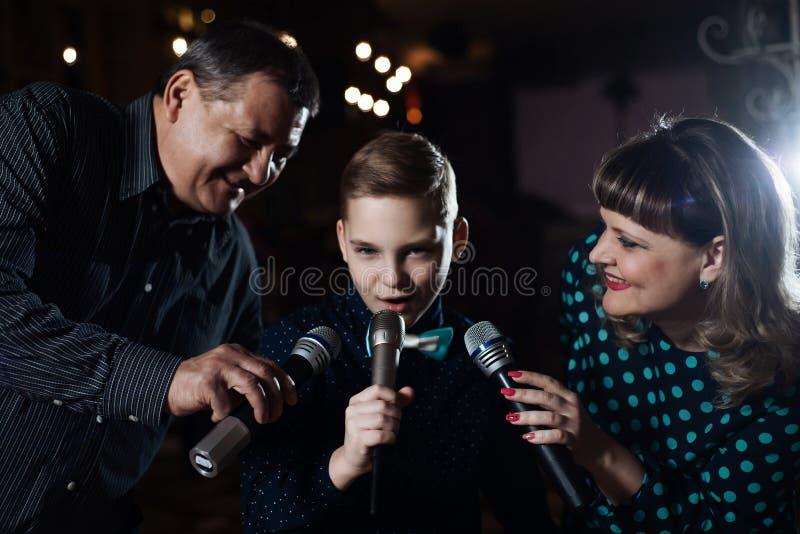 Karaoke de famille Portrait d'une famille heureuse, chantant dans des microphones photographie stock