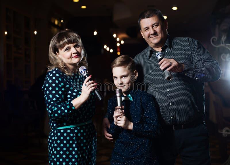 Karaoke de famille Portrait d'une famille heureuse, chantant dans des microphones photo stock