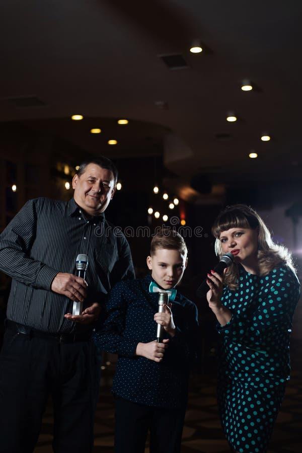 Karaoke de famille Portrait d'une famille heureuse, chantant dans des microphones photos libres de droits