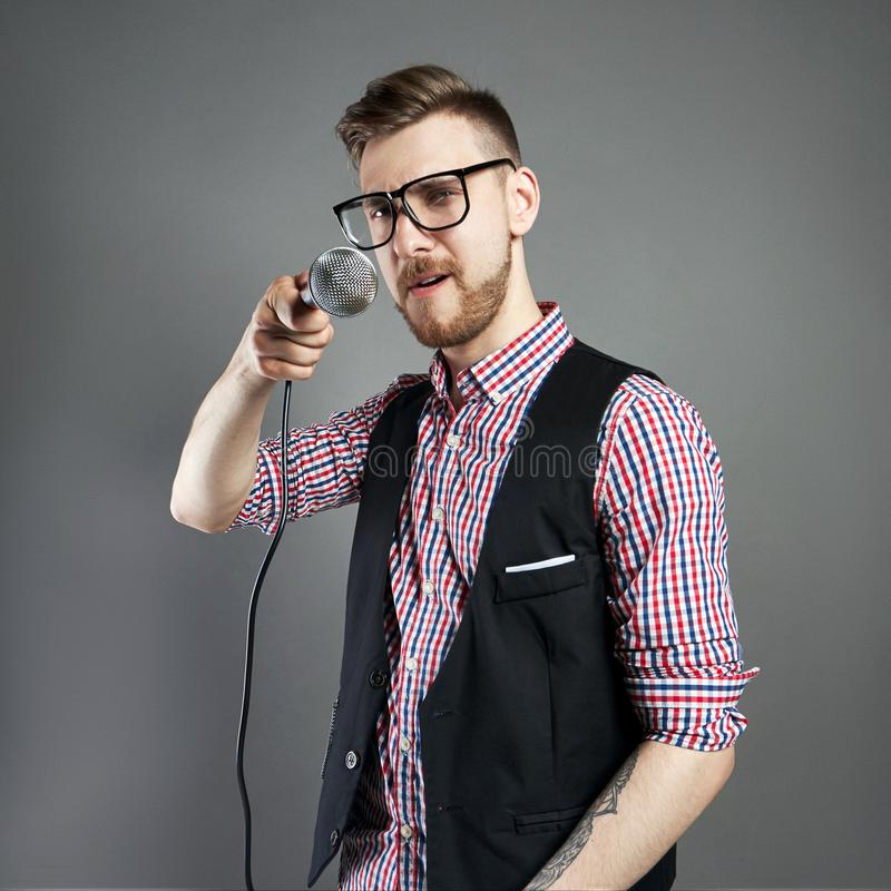 Karaoke man sings the song to microphone, singer with beard on g stock photos
