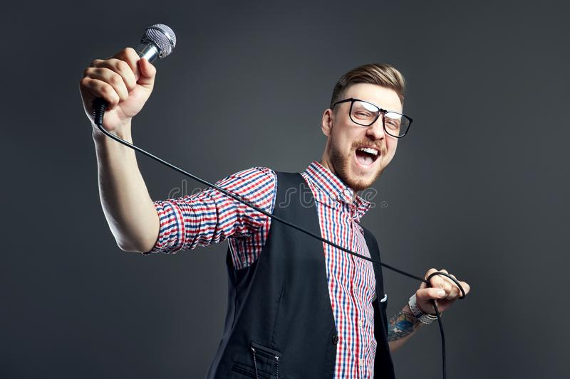 Karaoke man sings the song to microphone, singer with beard on grey background. Funny man in glasses holding a microphone. In his hand at the karaoke singer royalty free stock photography
