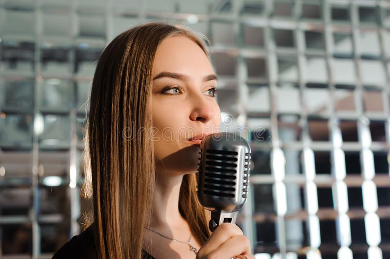 Karaoke party. Beauty girl with a microphone singing. Disco part royalty free stock images