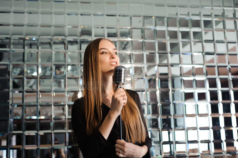 Karaoke party. Beauty girl with a microphone singing. Disco party. Celebration. stock photos