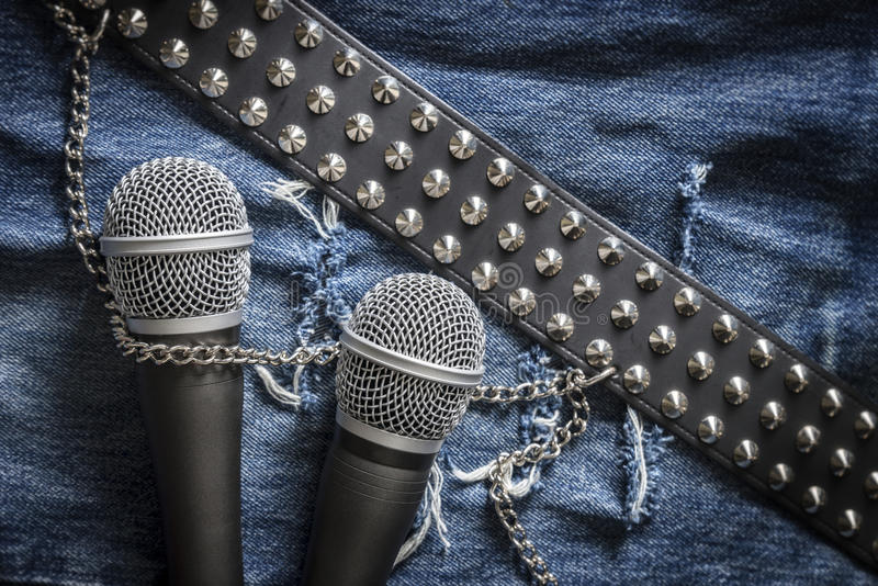 Karaoke / singer / rock band. Creative karaoke / singer / rock band Two microphones and a studded belt on jeans fabric royalty free stock photos