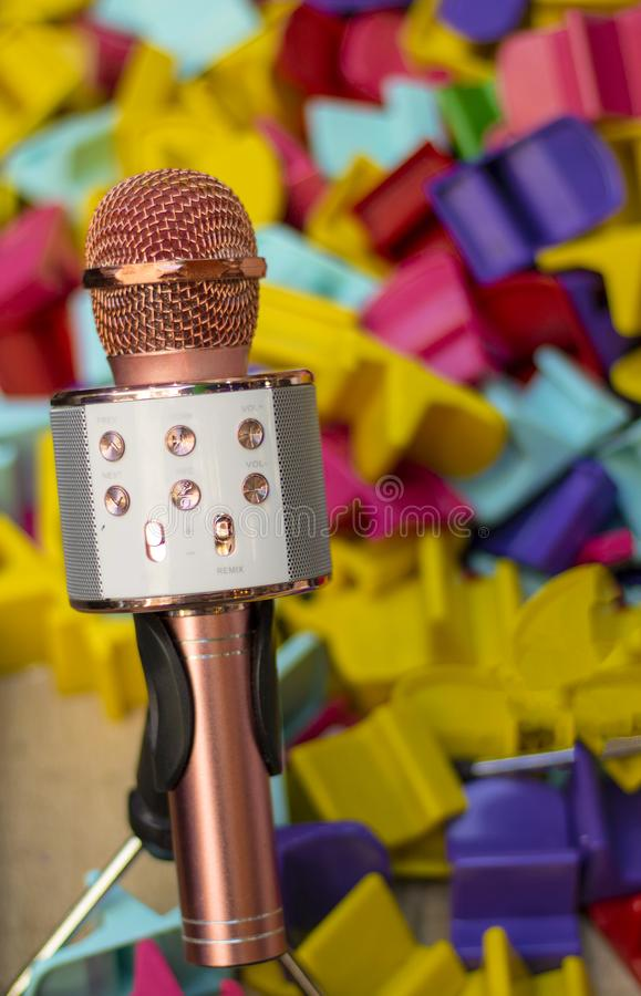 Karaokemicrofoon in roze en stuk speelgoed delen op achtergrond stock fotografie