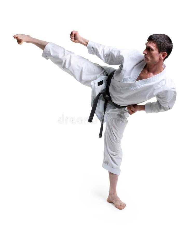 Karatè. L'uomo in un kimono colpisce il piede immagine stock libera da diritti