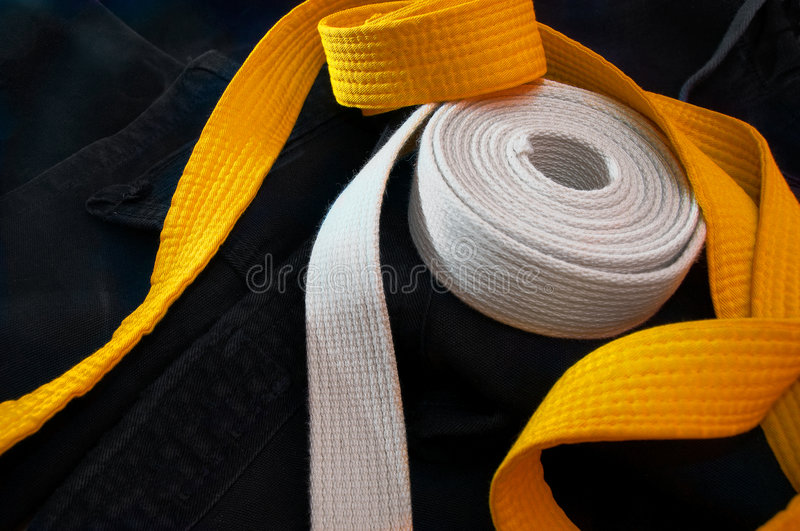 Karate beginner's belts. White and yellow karate belts coiled on a folded black gi royalty free stock images