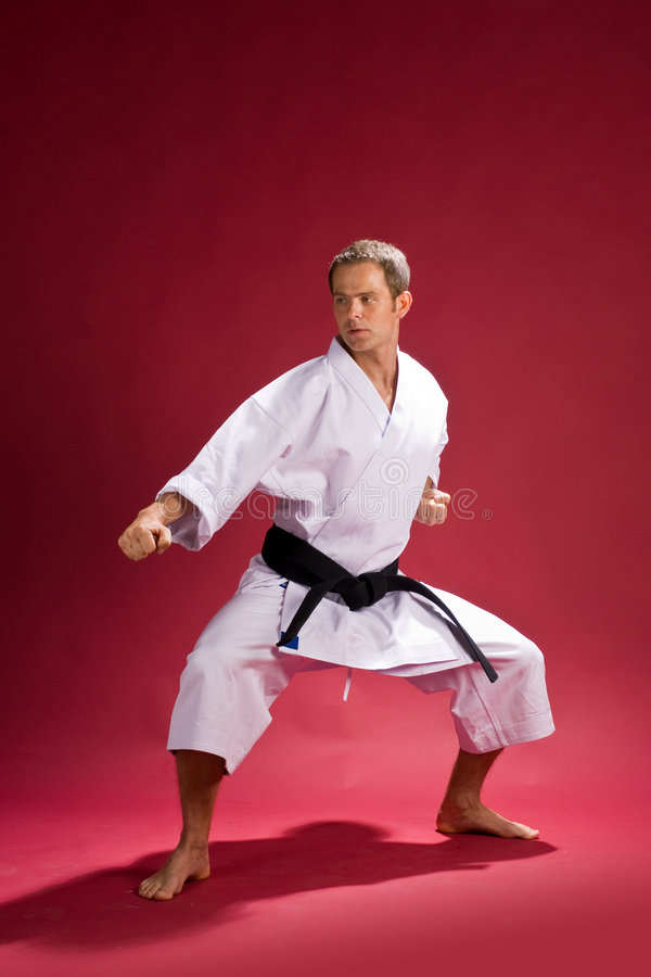 Karate black belt in kimono. Karate black belt wearing white kimono in defensive stance, red background royalty free stock image