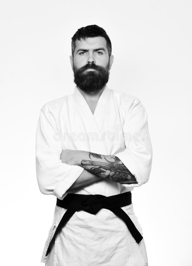 Karate boy. Judo master with black belt holds arms crossed. Man with beard in white kimono on white background. Karate man with serious face in uniform royalty free stock photography