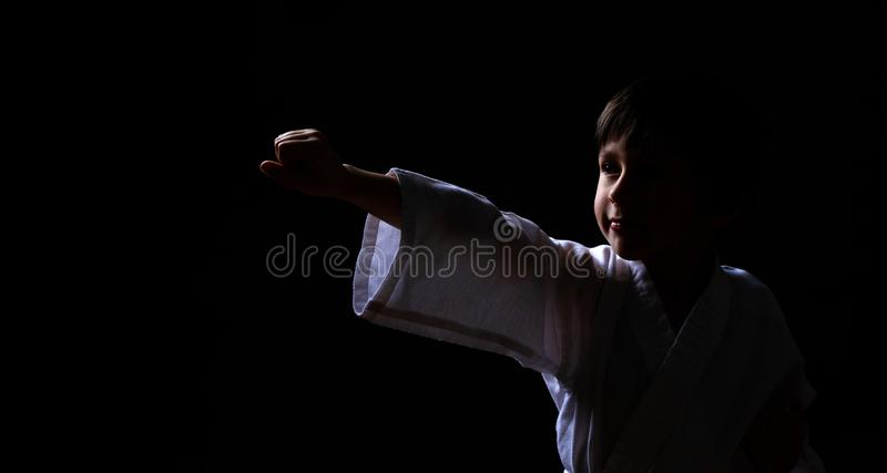 A karate boy in white kimono posing on dark background. Child ready for martial arts fight. Kid fighting at Aikido training. Best royalty free stock images