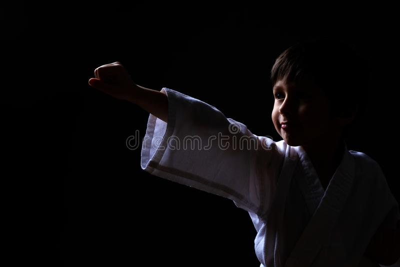 Karate boy in white kimono posing on dark background. Child ready for martial arts fight. Kid fighting at Aikido training. Best. For martial fights and sports stock image