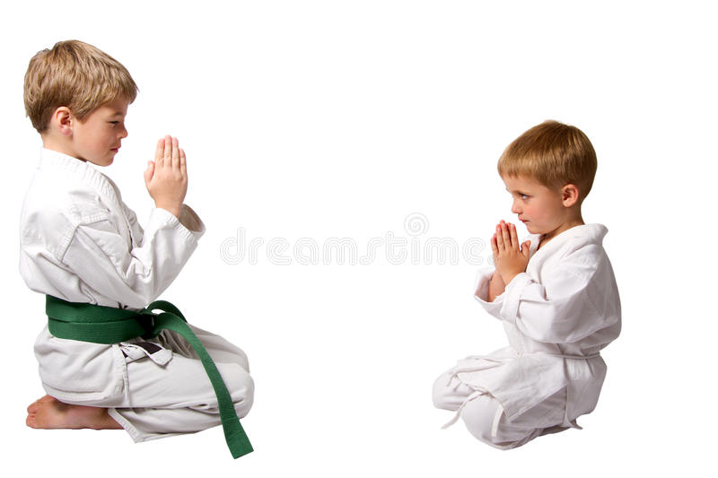 Karate buddies bowing. Two karate boys facing each other bowing isolated on a white background royalty free stock image