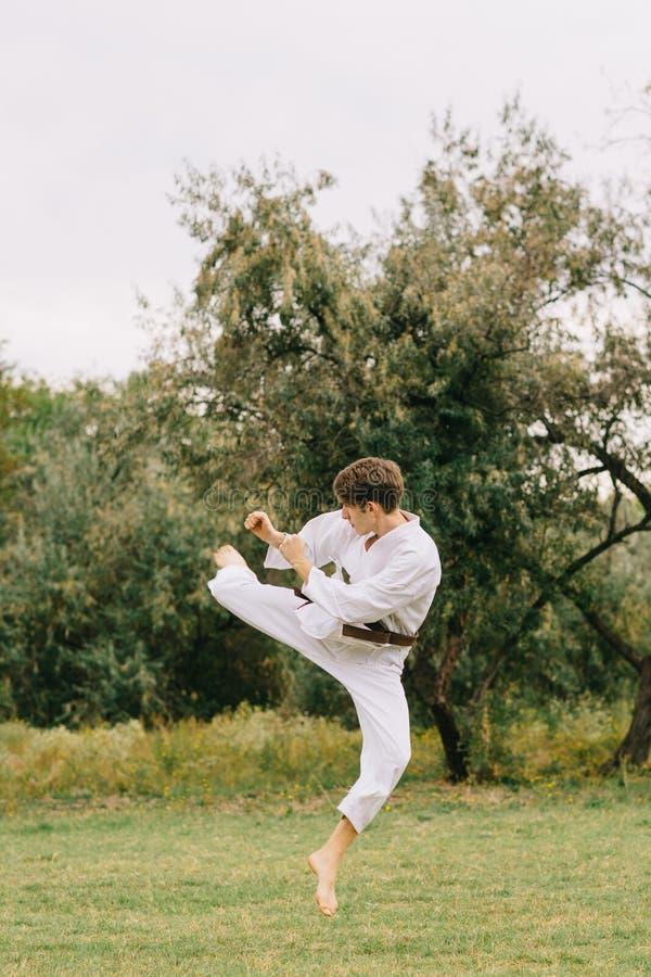 Karate chłopiec w akci Dżudo szkolenie na parkowym tle Walczący pojęcie kosmos kopii obrazy stock