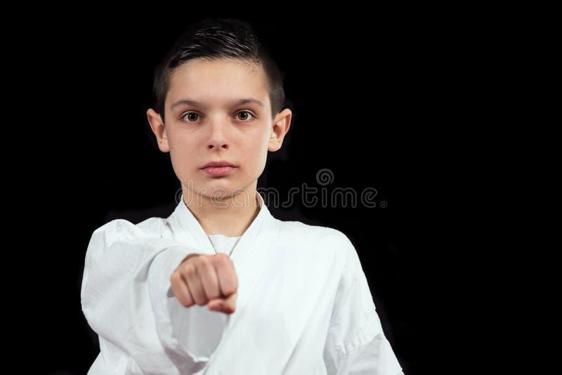 Karate chłopiec w białym kimonowym boju odizolowywającym na czarnym tle obraz stock