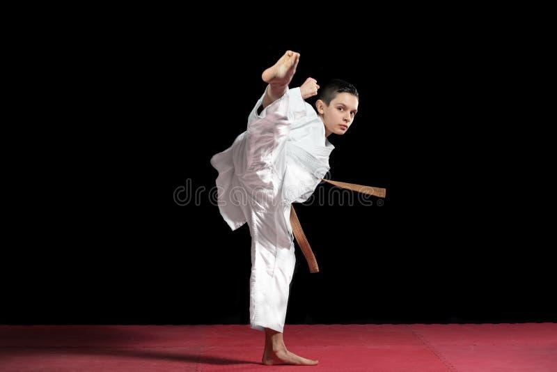 Karate chłopiec w białym kimonowym boju odizolowywającym na czarnym tle fotografia royalty free