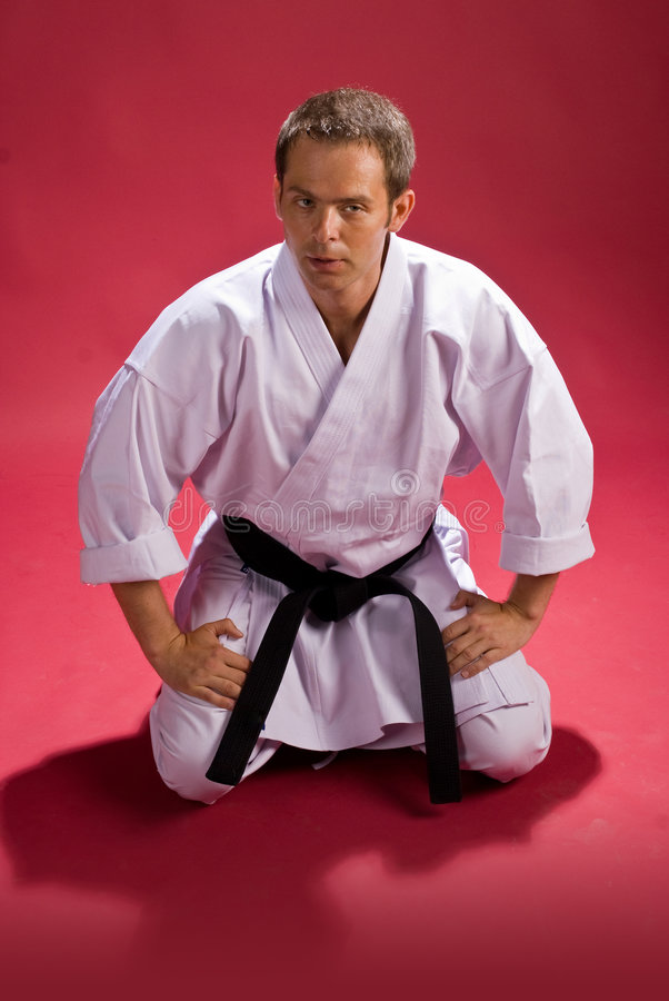 Karate Fighter. A man in a Karate Kimono with black belt(level) sitting down, on a red background stock photo
