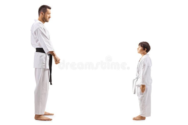 Karate garoto de pé olhando seu instrutor de karatê fotos de stock
