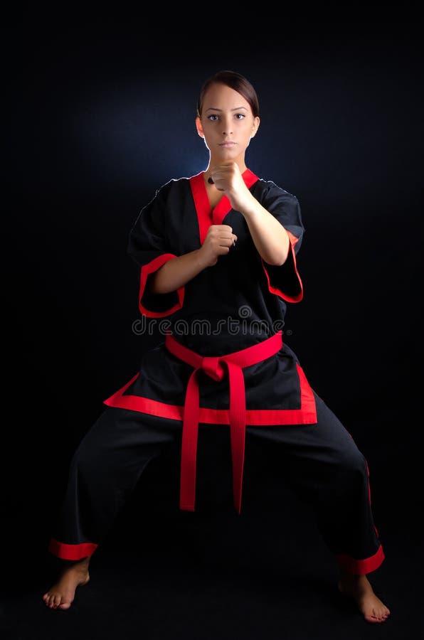 Karate Girl in Kimono. Karate girl posing in kimono against a black background royalty free stock images