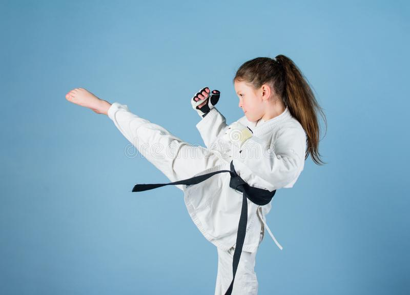 Karate gives feeling of confidence. Strong and confident kid. She is dangerous. Girl little child in white kimono with. Belt. Karate fighter ready to fight stock photo