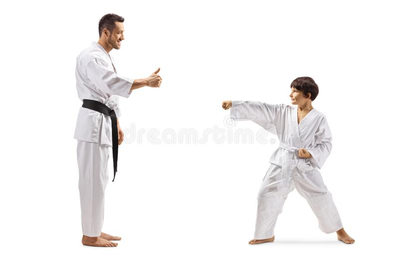 Karate instructor giving a thumb up to a boy exercising royalty free stock photo