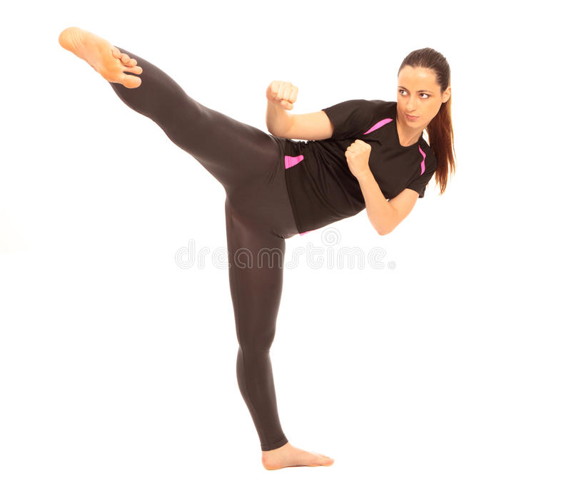Karate Kick. A young female dressed in gym clothes performing a martial arts kick on isolated white background royalty free stock images