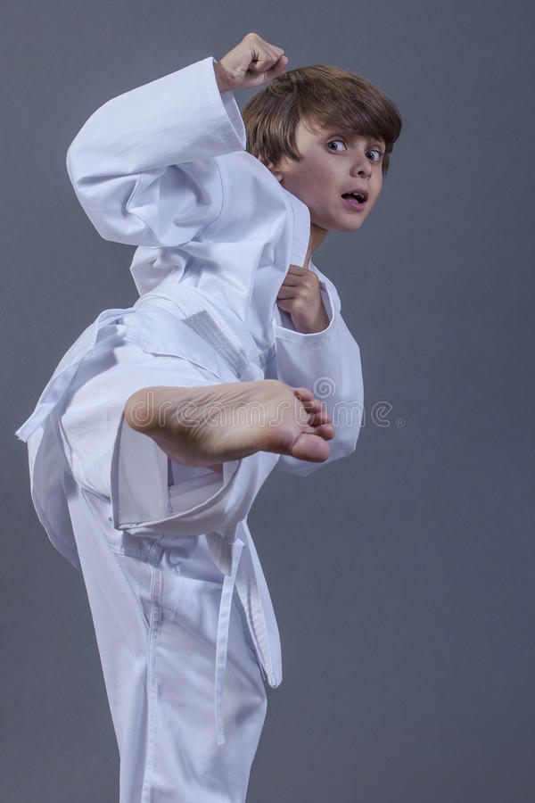 Karate kick. Young handsome Caucasian boy with scared expression performs side kick in karate uniform with white belt on grey background stock photography