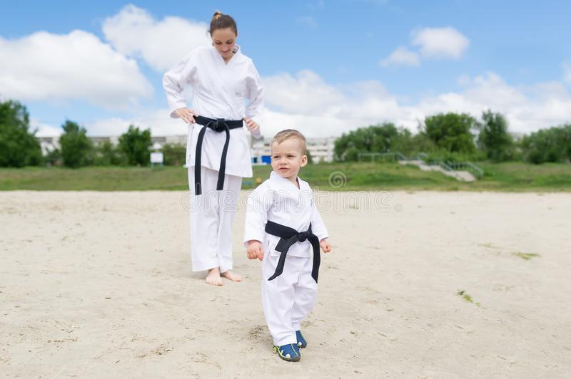 Karate kid - portrait of little boy in the kimono. The boy`s mother is in a kimono at a background. royalty free stock photography