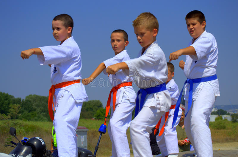 Karate kids demonstration. Sportsman in karategi are hitting blows arms demonstrating the techniques of Karate Kyokushin martial art during a show at Varna stock photo