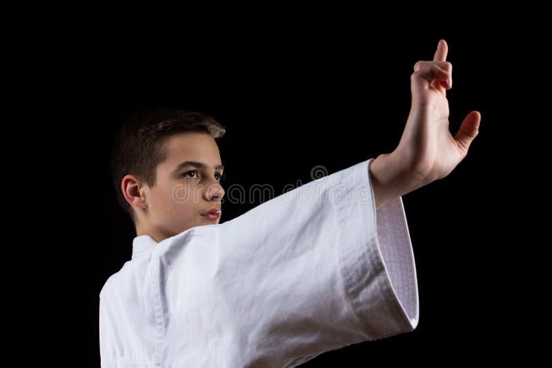 Karate krijgssport met jonge jongen in kimono, zwarte achtergrond, arts. royalty-vrije stock foto