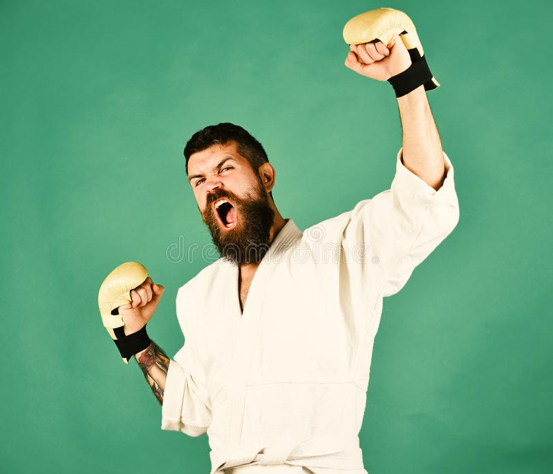 Karate man with angry face in golden boxing gloves. stock photos