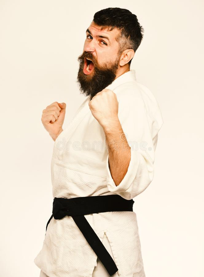 Karate man with angry face in uniform. Man with beard. In white kimono on white background. Judo master with black belt practices attack posture and yells stock image