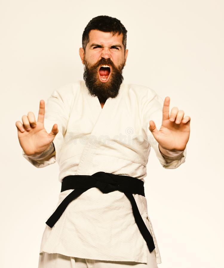 Karate man with angry face in uniform. Oriental sports concept. Jiu Jitsu master with black belt. Practices attack or defense posture. Man with beard in white stock photo