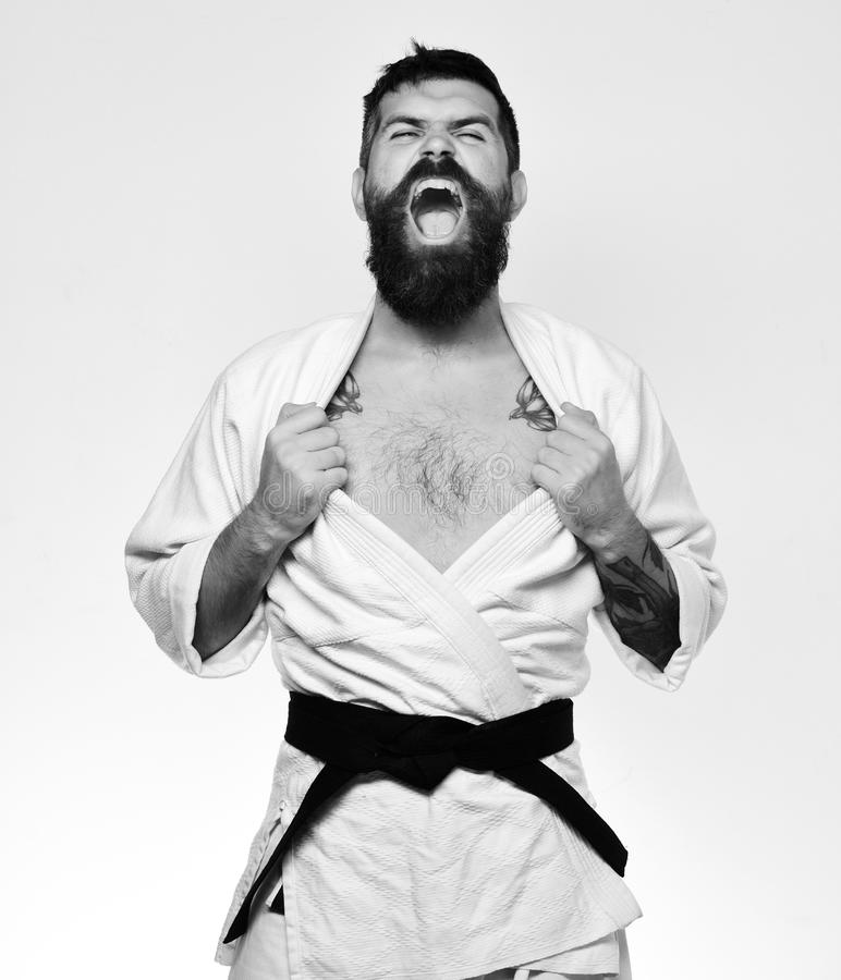 Karate man with angry face in uniform. Oriental sports concept. stock image