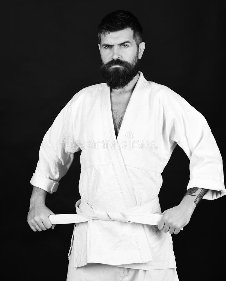 Karate man. Man with beard in white kimono on black background. Healthy lifestyle and sports concept. Karate man with strict face in uniform. Jiu Jitsu master stock photos