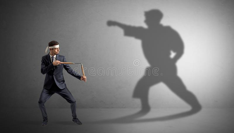 Karate man confronting with his own shadow. Young karate man confronting with his own shadow royalty free stock photos