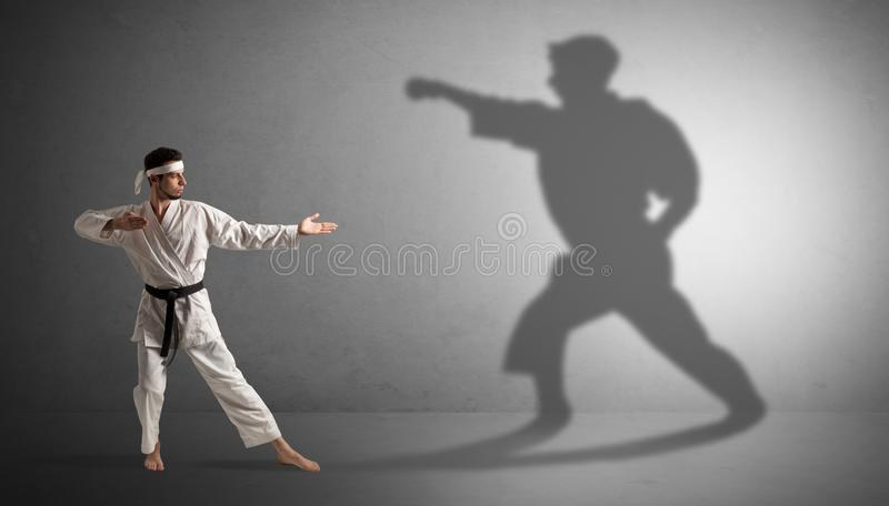 Karate man confronting with his own shadow. Young karate man confronting with his own shadow royalty free stock images
