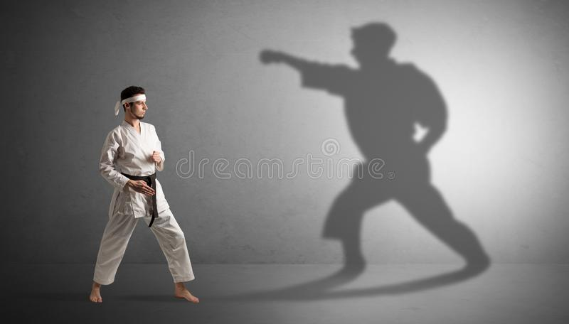 Karate man confronting with his own shadow. Young karate man confronting with his own shadow stock image