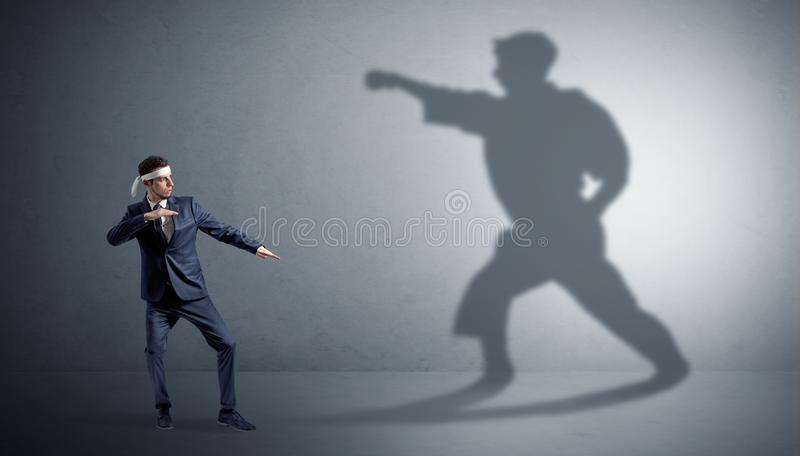 Karate man confronting with his own shadow. Young karate man confronting with his own shadow stock photo