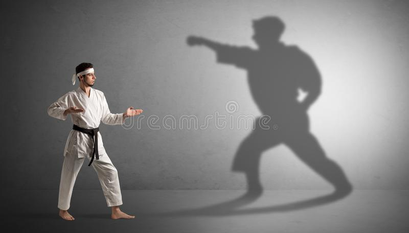 Karate man confronting with his own shadow. Young karate man confronting with his own shadow stock images