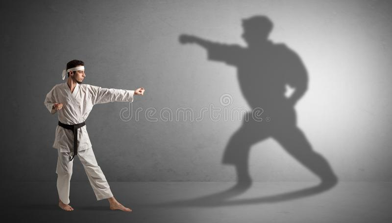 Karate man confronting with his own shadow. Young karate man confronting with his own shadown stock image