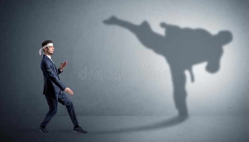Karate man confronting with his own shadow. Young karate man confronting with his own shadown stock photography