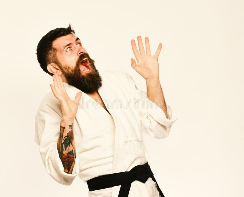 Karate man with scared face in uniform. Man with beard. In white kimono on white background. Oriental sports concept. Taekwondo master puts hands up in fear and royalty free stock photography