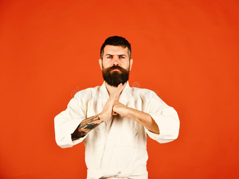 Karate man with serious face in uniform. Man with beard. In white kimono on red background. Jiu Jitsu master puts fist into palm in traditional greeting stock image
